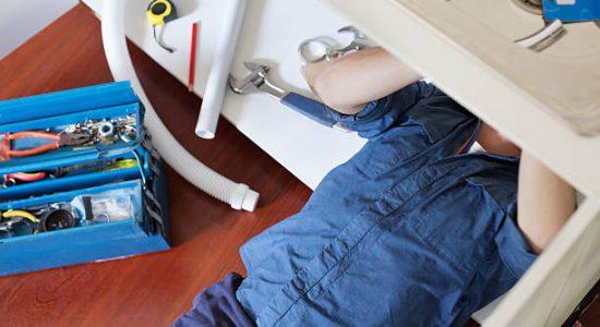 Plombier qui réalise des travaux de rénovation de plomberie sous un évier