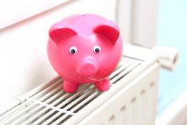 Tirelire en forme de cochon posée sur un radiateur pour symboliser des économies d'énergie