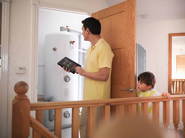 Père de famille qui contrôle la consommation de la chaudière dans sa maison